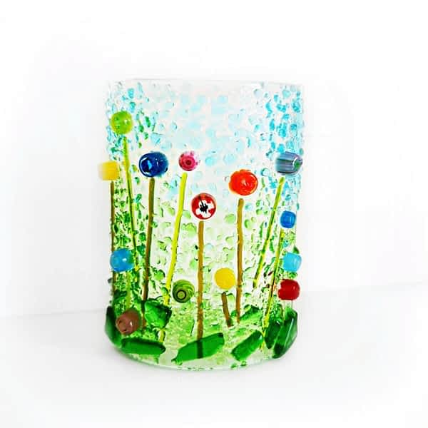 A curved freestanding ornament featuring a rainbow wildflower meadow with green grass and blue sky.