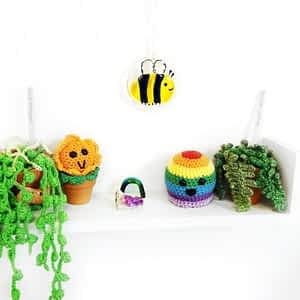 A bumblebee suncatcher with a smile made from glass on a white background. Features iridescent glass for the wings and black sparkly glass for the body.