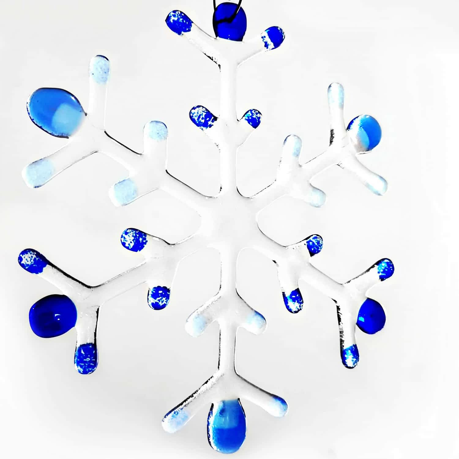 A light and dark blue fused glass large snowflake hanging on a white background