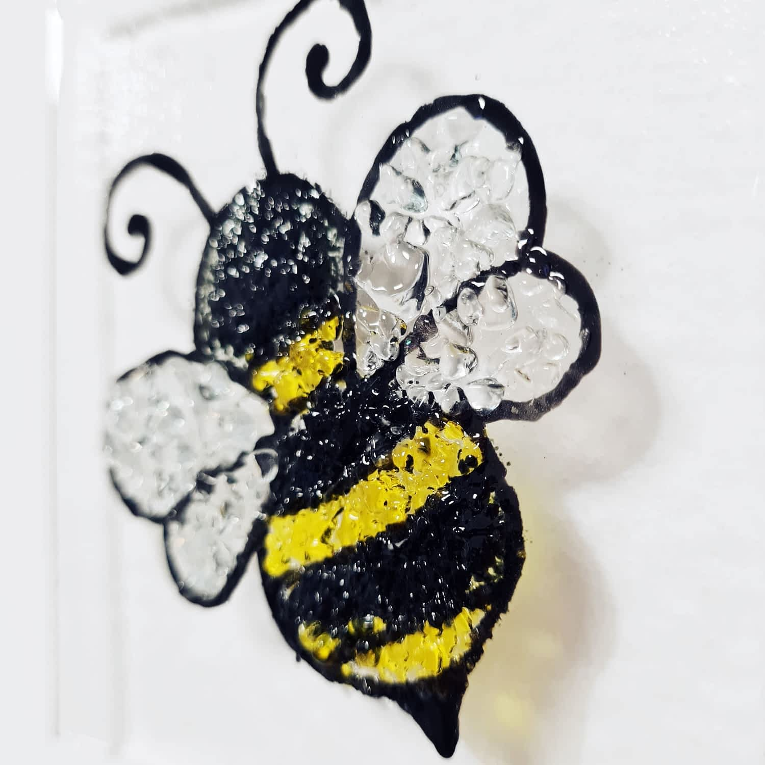 A wonderful suncatcher image of a bee made out of black, yellow and clear glass.