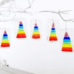 """5 fused glass hanging christmas decorations featuring a rainbow christmas tree and white """"snow"""" hanging from a white tree branch."""