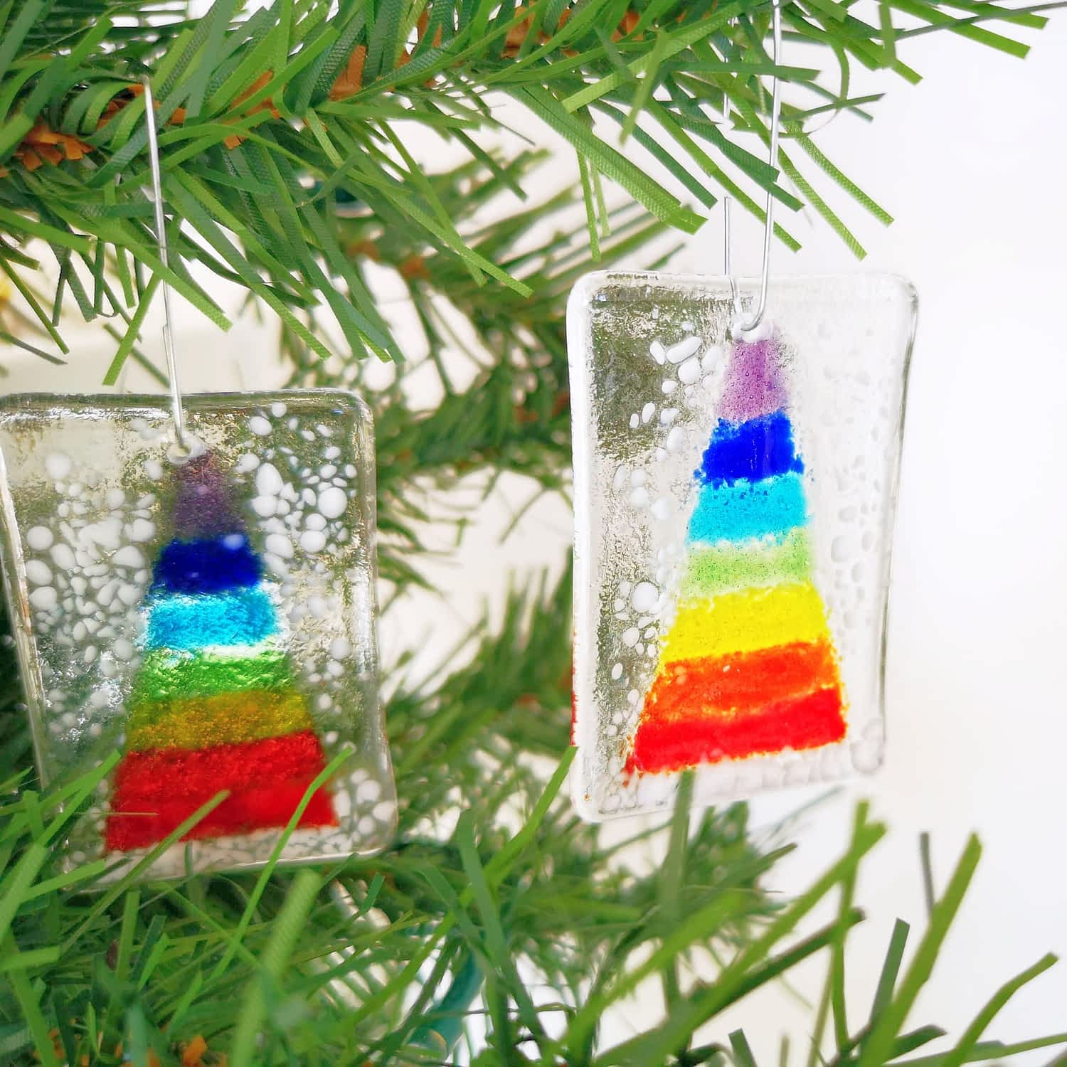 """2 fused glass hanging christmas decorations featuring a rainbow christmas tree and white """"snow"""" hanging from a green christmas tree."""