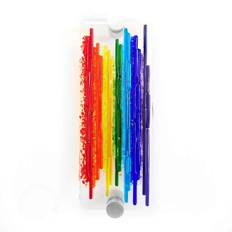 A textured rainbow wall panel on clear glass with silver standoffs.