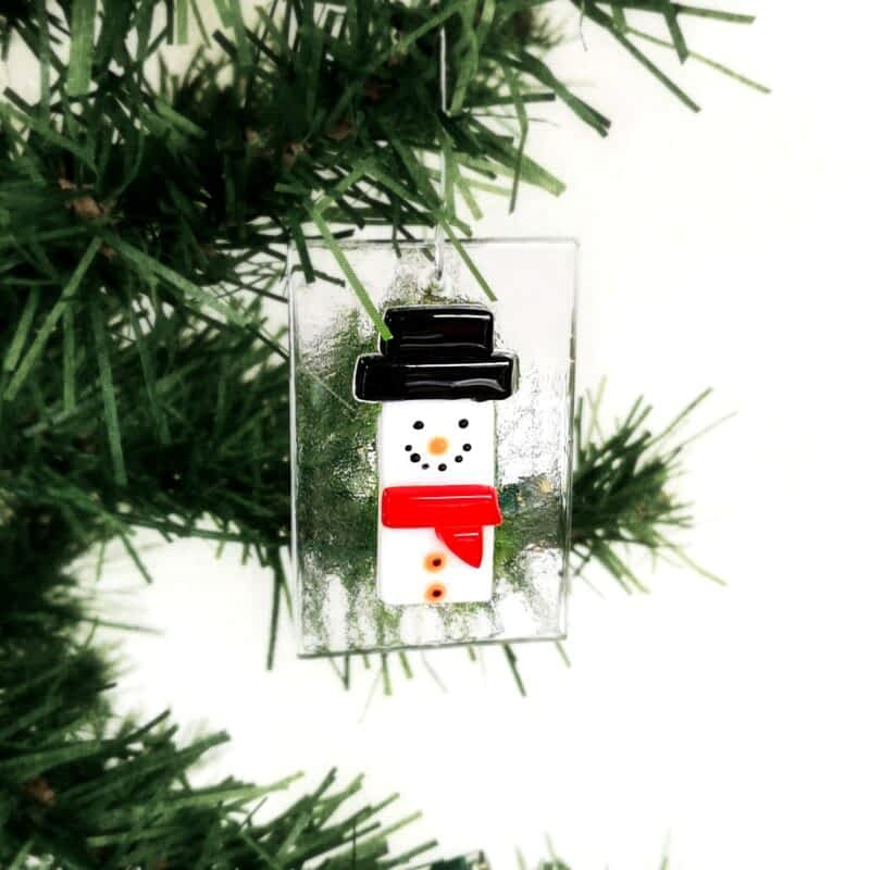 A white snowman hanging ornament with a black hat and red scarf on a clear glass base.