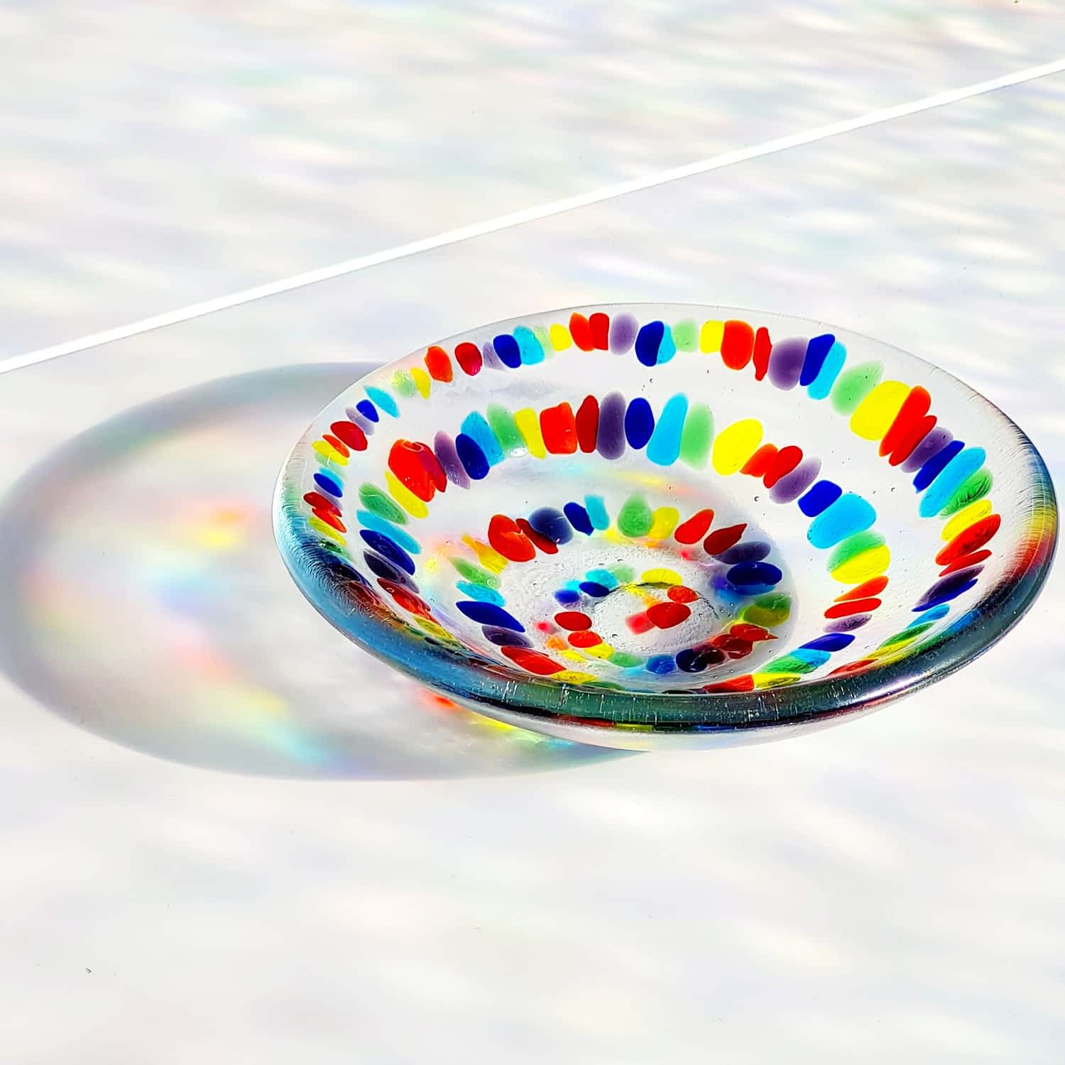 A Spiral Rainbow Bowl showing Rainbow coloured shadows on a white background