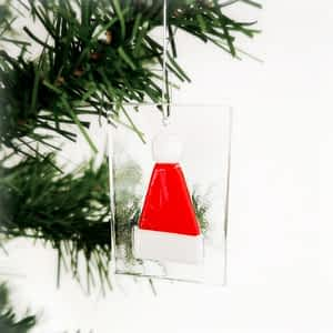 A red and white santa hat hanging ornament on a clear glass base