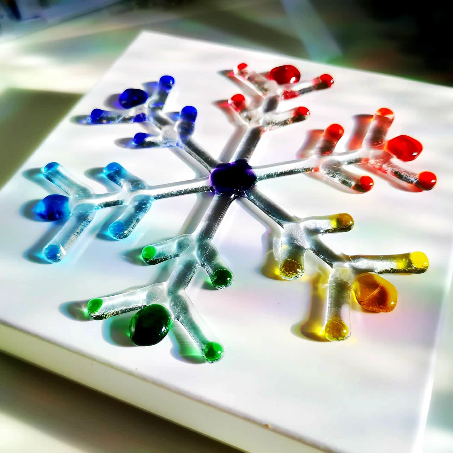 A rainbow and clear fused glass large snowflake with a white background.