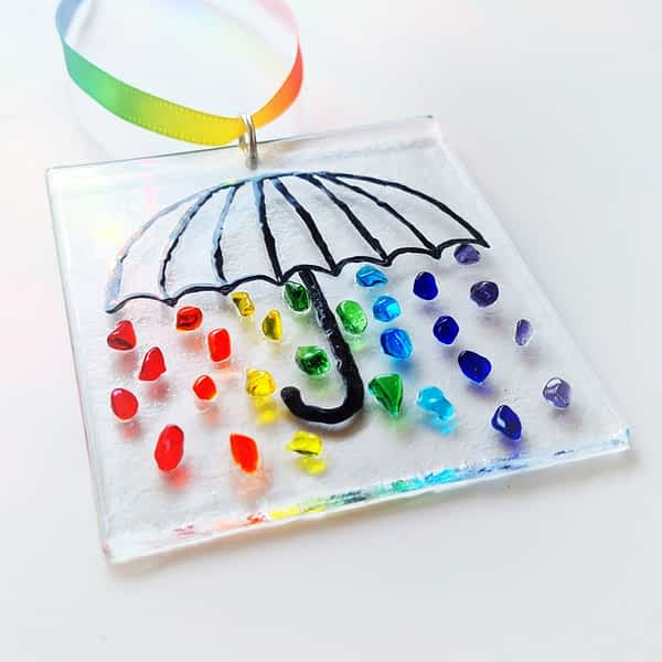 A Hanging suncatcher featuring a black umbrella with rainbow coloured raindrops.