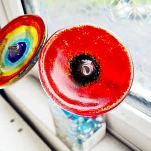 A striking red poppy made of glass.