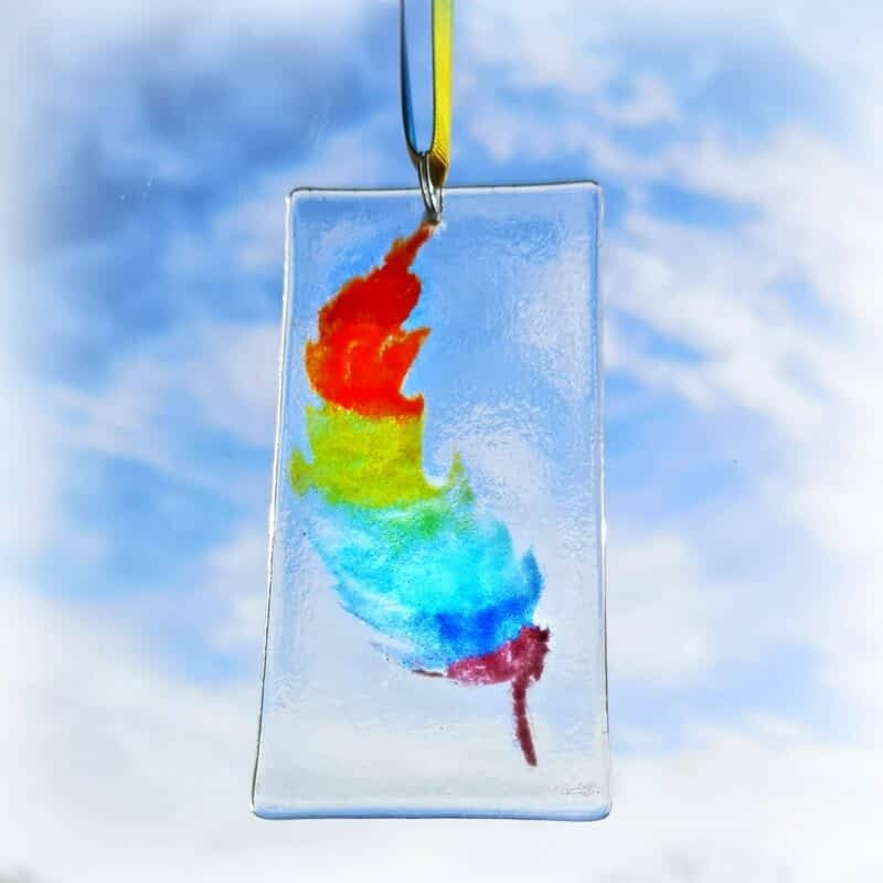 A Rainbow coloured feather on clear glass with rainbow ribbon, hanging on a white background.