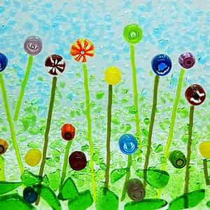 A suncatcher featuring a blue sky, green grass and rainbow wildflowers. All textured to give a sense of depth.