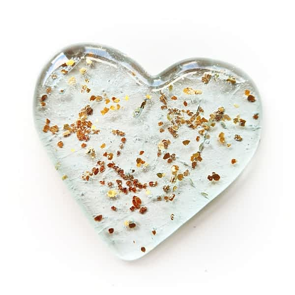 Cremation Ashes fused inside a clear heart with a sprinkling of gold glitter, on a white background.