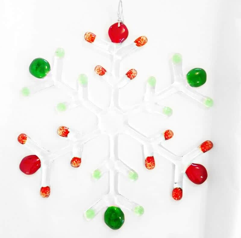 A large clear snowflake with Red and Green coloured tips hanging on a white background.