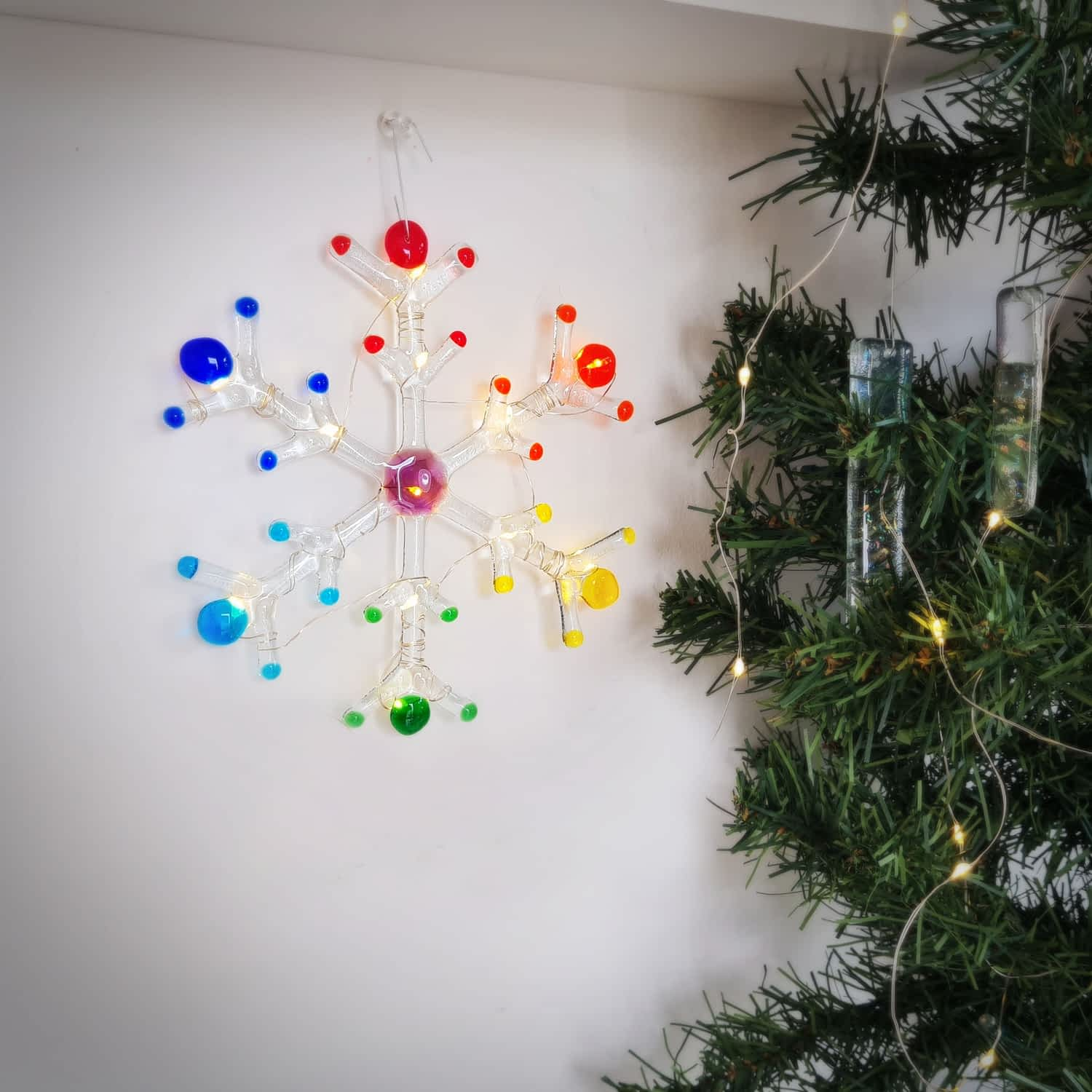 A handmade fused glass snowflake with rainbow colours and warm white leds on a white background with a green christmas tree.