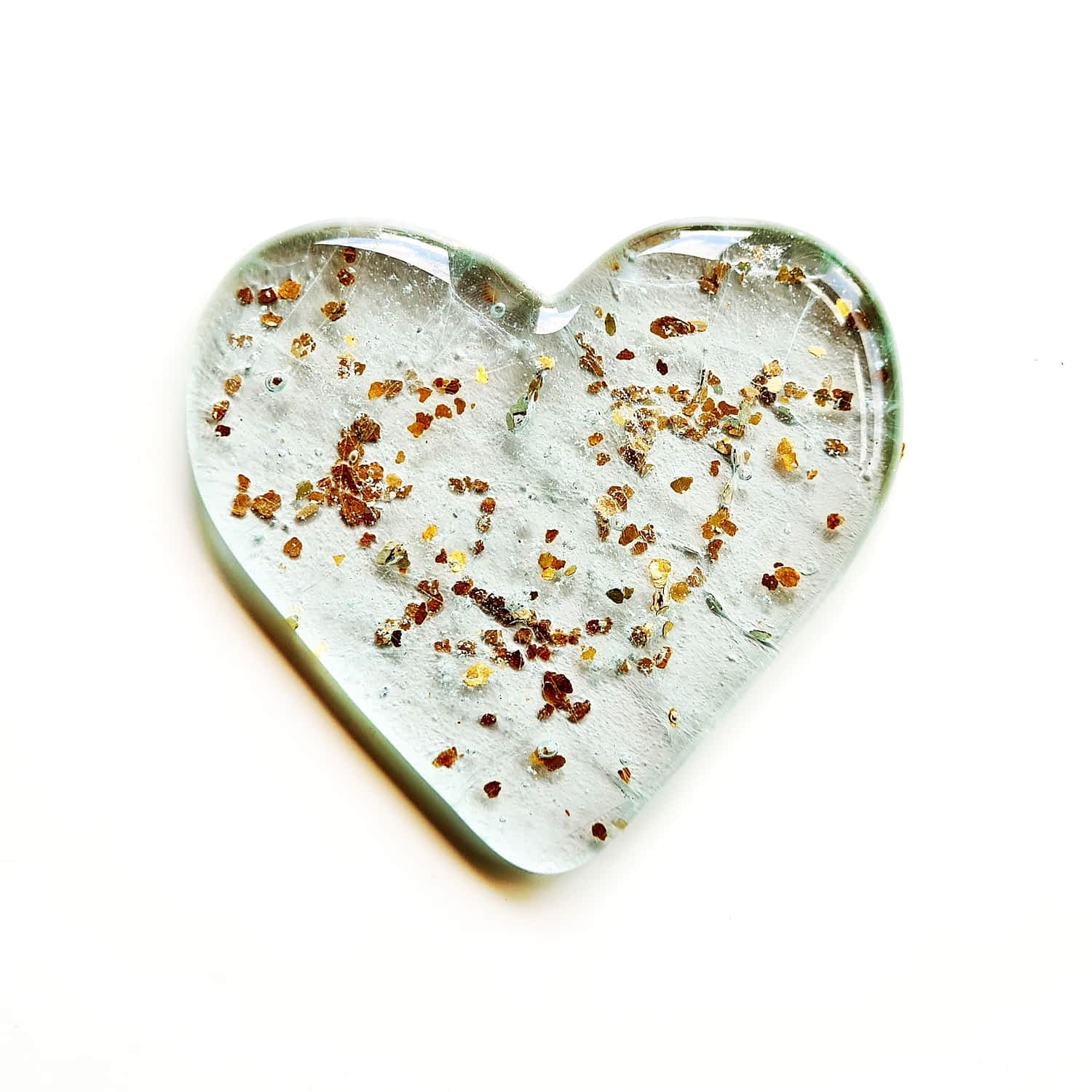 Pet Cremation Ashes fused inside a clear heart with a sprinkling of gold glitter, on a white background.