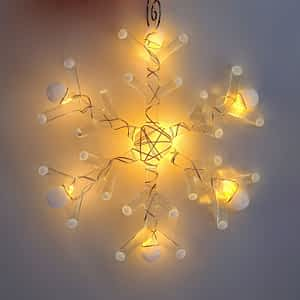A handmade fused glass snowflake with white tips and warm white led lights on a white background.