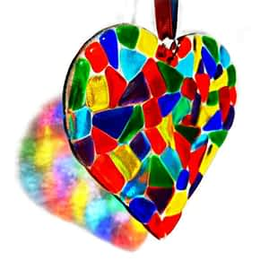 A beautiful, bright and colourful large rainbow heart made using rainbow coloured glass, hanging with rainbow ribbon.