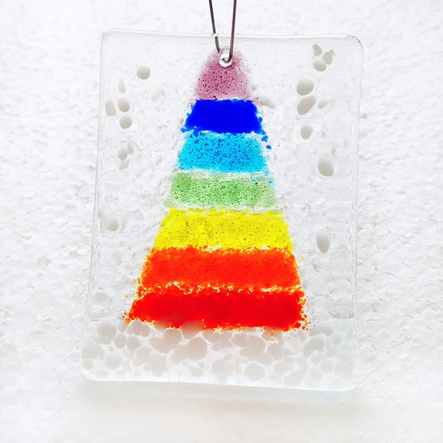 """A fused glass hanging christmas decoration featuring a rainbow christmas tree and white """"snow"""""""
