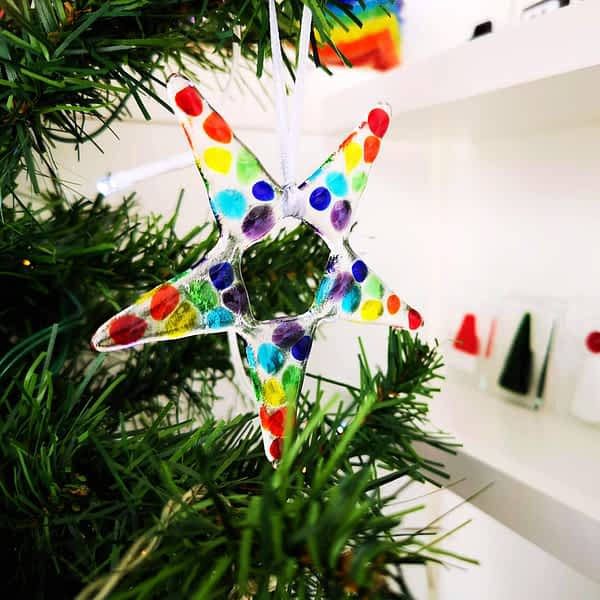 A fused glass rainbow star christmas decoration hanging from a christmas tree branch.