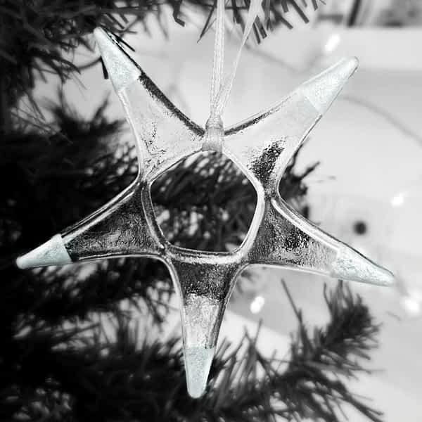 Silver Fused Glass Star Ornament hanging on a Christmas tree with twinkling lights in the background.