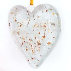 Cremation Ashes fused inside a clear hanging heart with a sprinkling of gold glitter, on a white background.