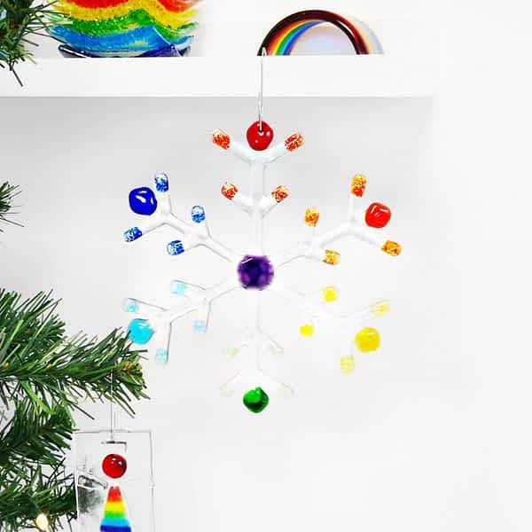 A large clear and Rainbow snowflake hanging from a shelf with a white background.