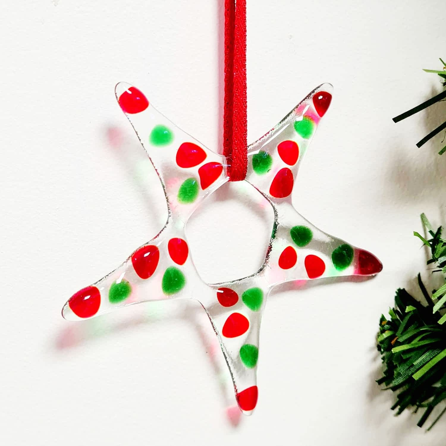 A red and green fused glass star christmas decoration on a white background.