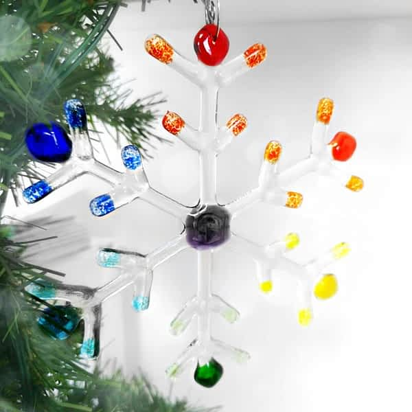 A large clear snowflake with Rainbow coloured tips hanging on a green christmas tree.