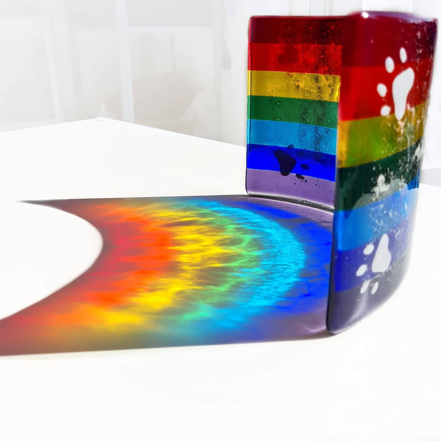 A Large rainbow bridge with cremation ashes fused inside, resting on a white background with the sun projecting a beautiful rainbow shadow.