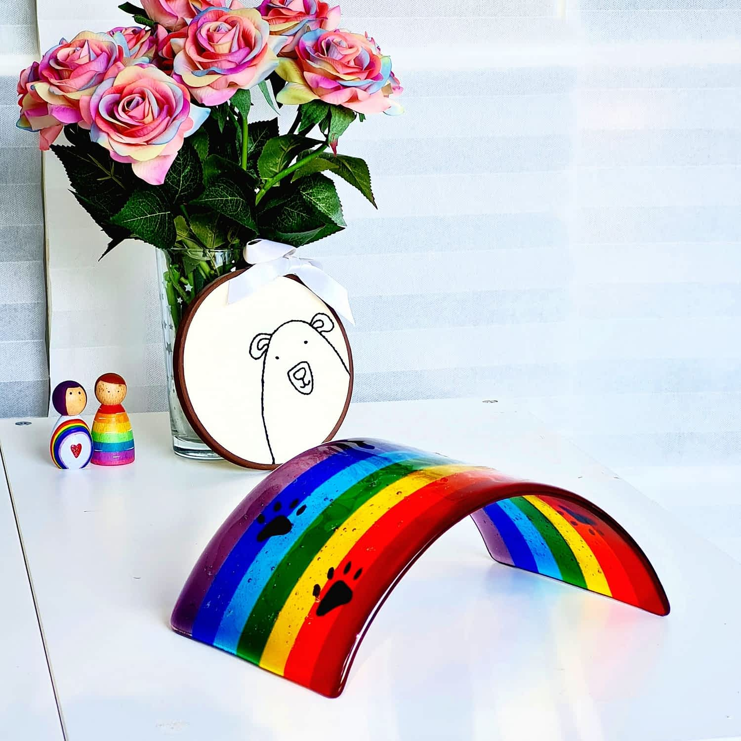 A glass Rainbow Bridge with black dog pawprints hand drawn in enamel on a white surface with rainbow peg dolls, rainbow flowers and a bear embroidery hoop in the background.