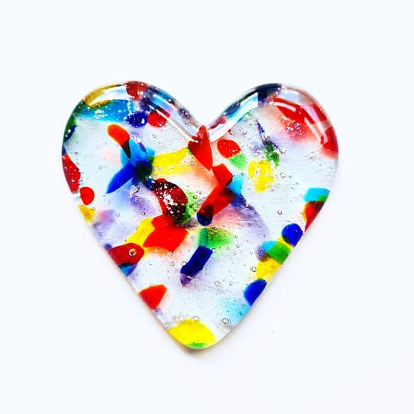 Cremation Ashes fused inside a clear glass heart with small pieces of coloured glass, on a white background.