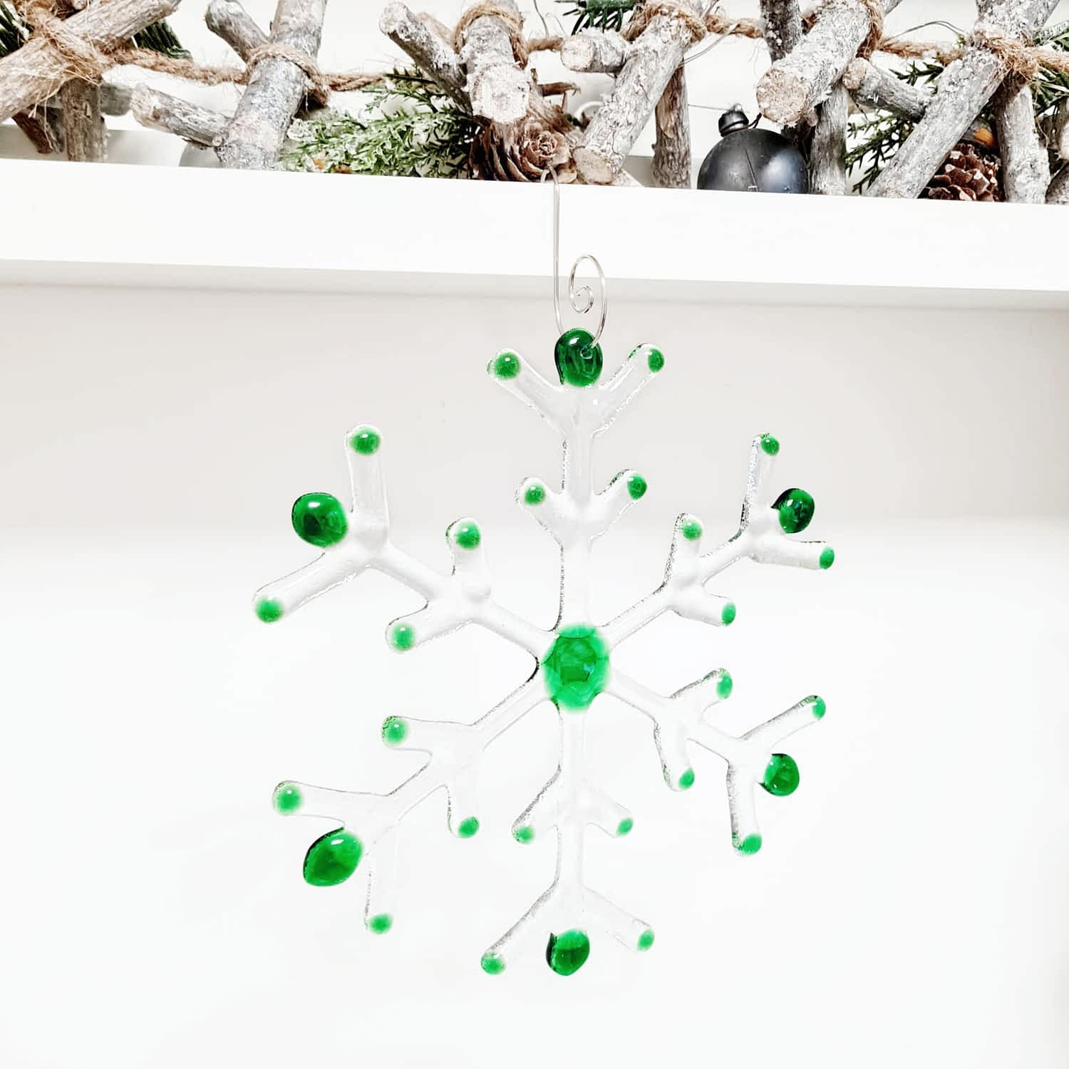 A green and clear fused glass large snowflake hanging on a white background