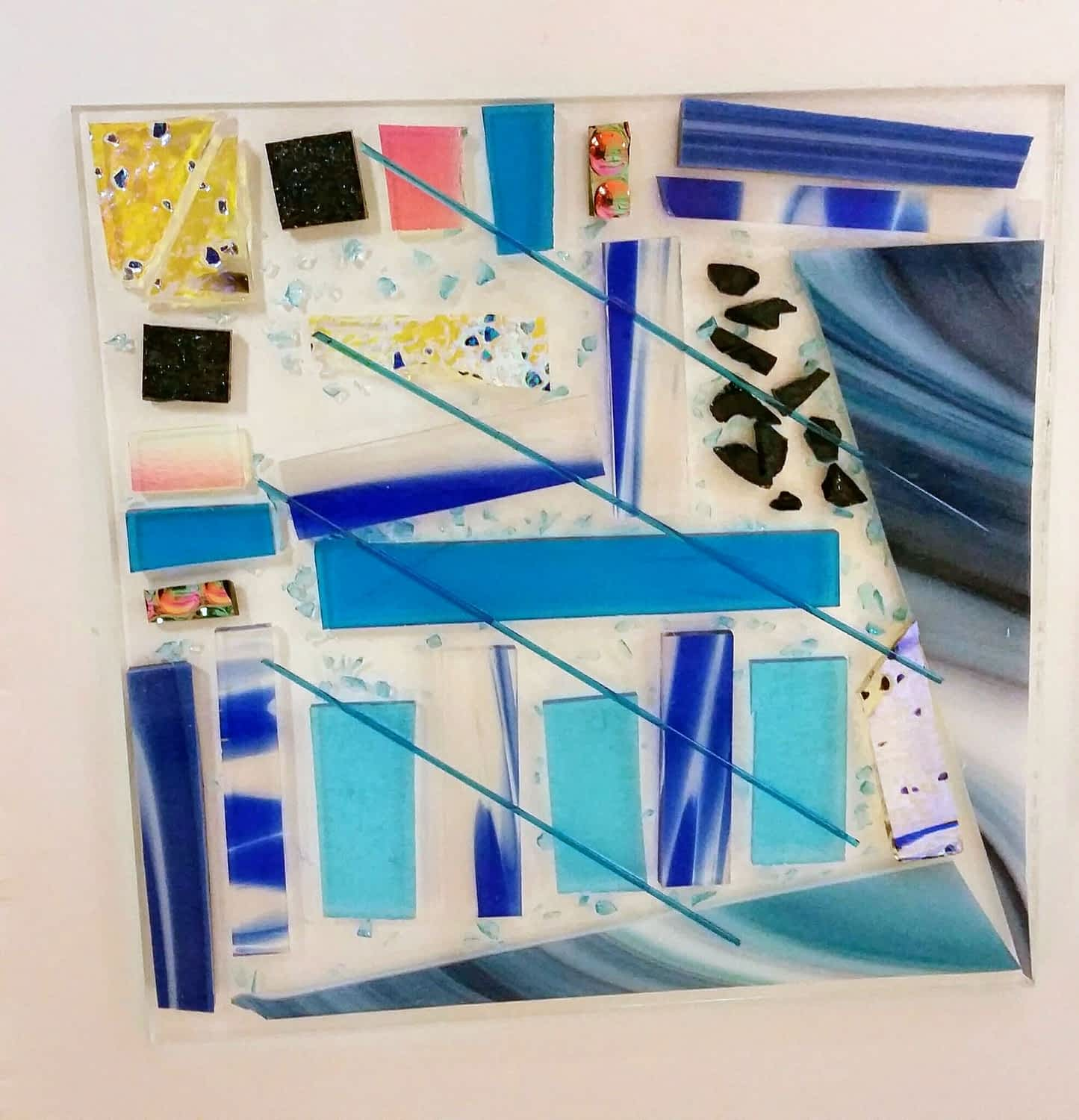 Lots of different shapes and colours of glass, a test tile for firing.
