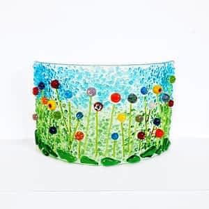 A beautiful curved piece of glass featuring Rainbow coloured wildflowers on a green and blue background.