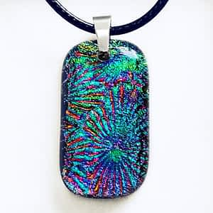 A stunning purple, blue, gold, green Dichroic glass necklace on a white background.