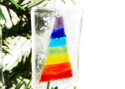 A photo of a glass Christmas Tree Ornament depicting a Christmas Tree in Rainbow colours with white snow at the base.