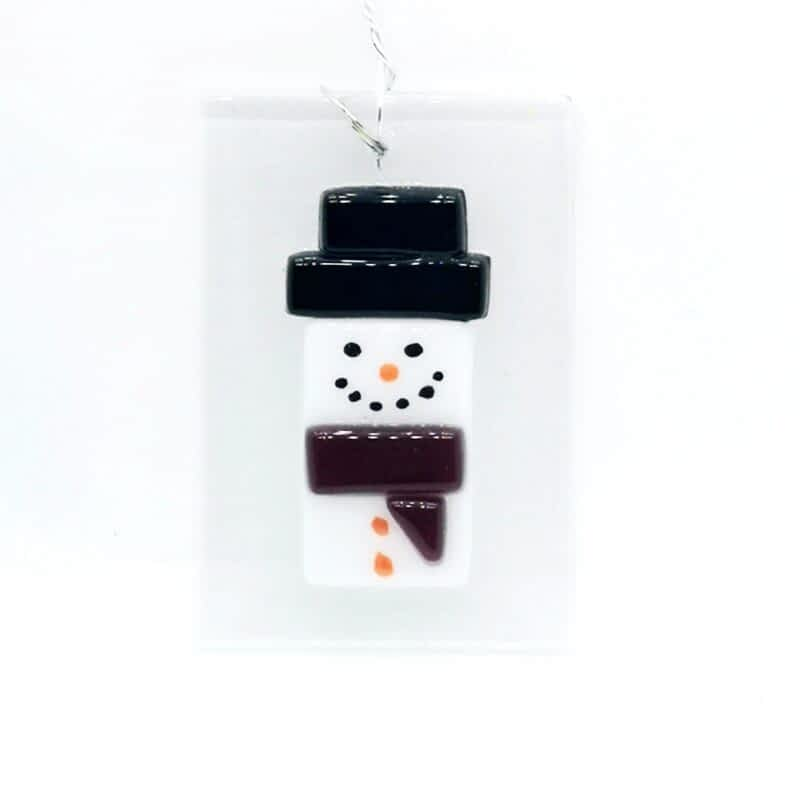 A fused glass snowman with a purple scarf, black hate and orange nose on a white background