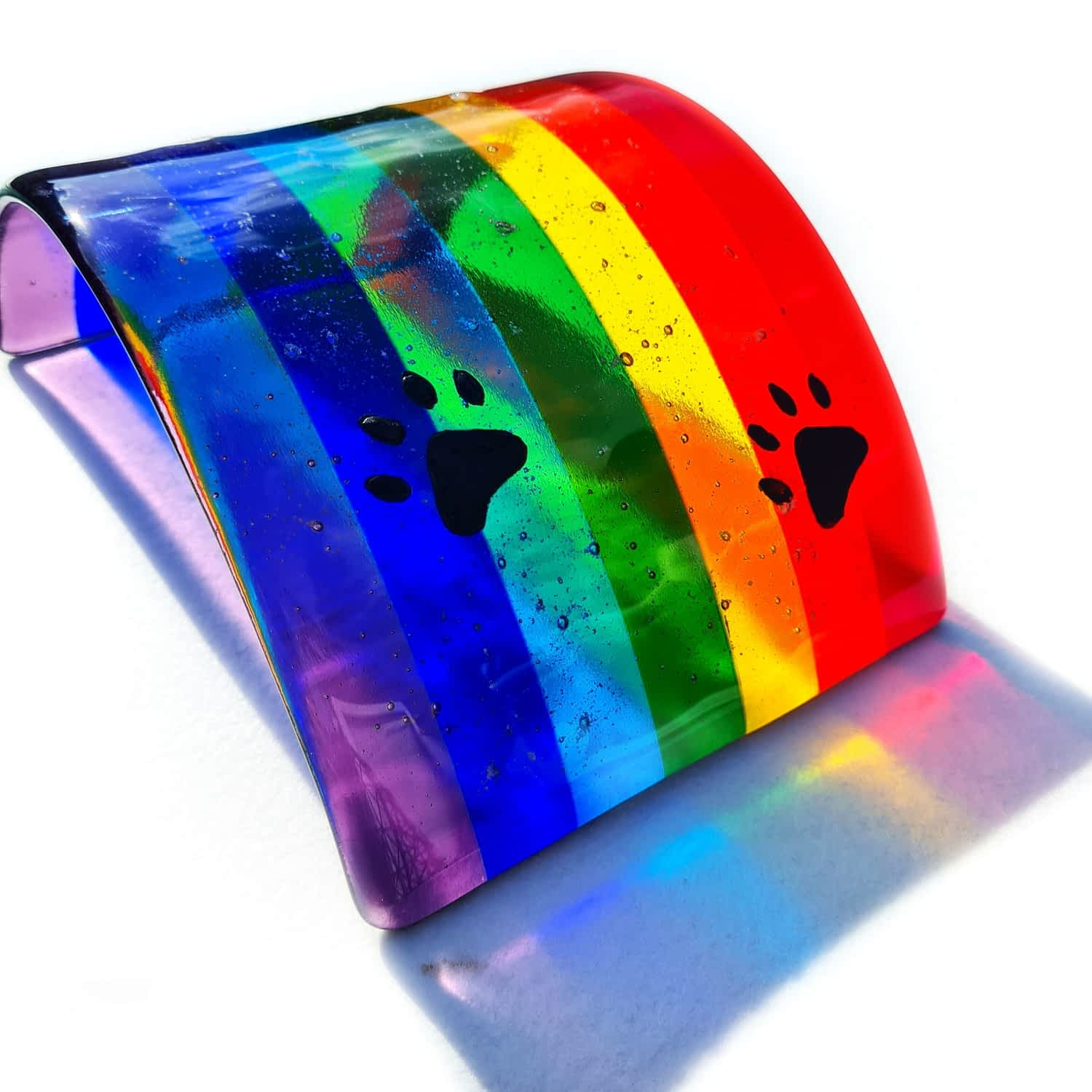 A glass Rainbow Bridge with black dog pawprints hand drawn in enamel with cremation ashes fused inside the glass.